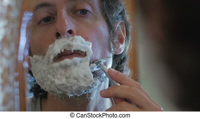 A man uses a safety razor to shave his beard - handheld - An...