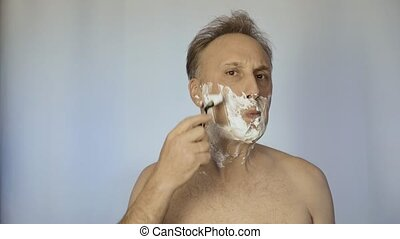 A man uses a sharp razor. He looks after his appearance....