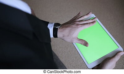 A man uses a tablet PC at his desk. Chroma key screen for...