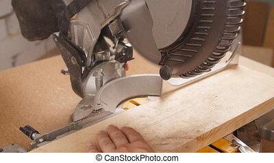 Electric circular saw cutting piece of wood in sawmill - A...