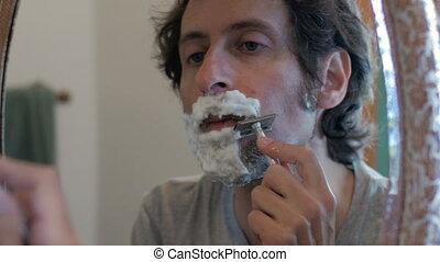 A man using a safety razor to shave in a mirror - dolly shot...