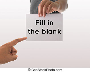 a man using hand holding the white paper with text fill in the blank