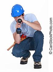 A man using his drill as a gun.