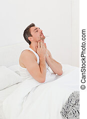A man waking up in his bedroom