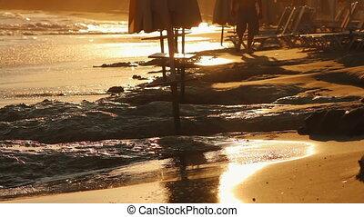 A man walking along the beach at su