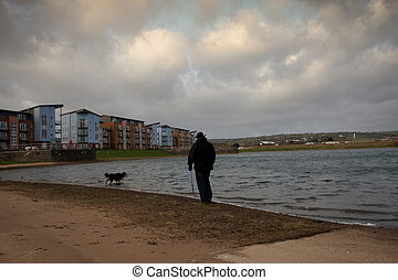 A man walking his border collie by a pond
