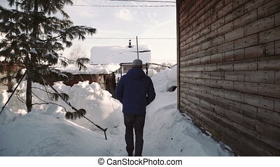 a man walking in the snow-covered lane. Wooden traditional house in winter village