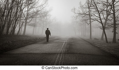 A man walks alone in the sooky fog in the winter forest