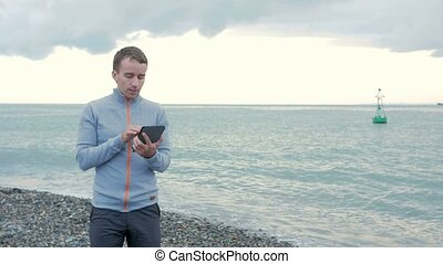 A man walks along the beach near the ocean with the tablet. He checks messages on the social network and browses photos.