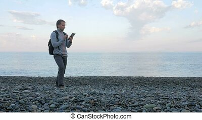A man walks along the beach near the ocean with the tablet.