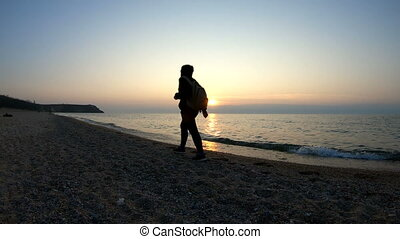 A man walks along the coast at sunset