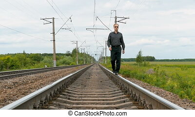 A man walks by rail.