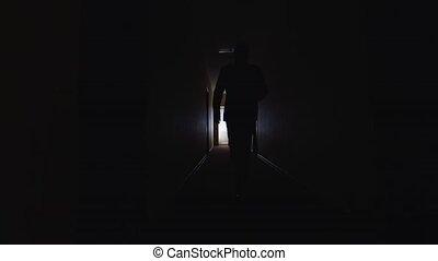 A man walks down the dark corridor