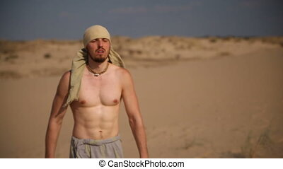 Man walking on hot sand under the scorching sun in the desert