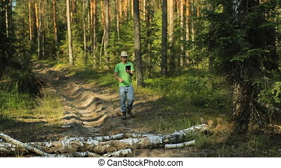 A man walks through the forest with a tablet PC and looking at the navigation application.