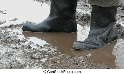 A man walks through the muddy puddle in rubber boots. - A...
