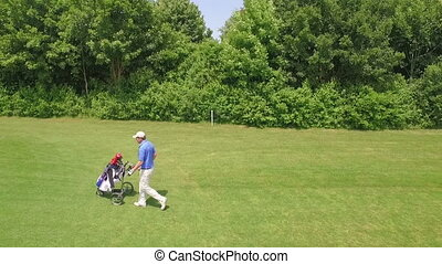 man walks with his caddy across the golf course