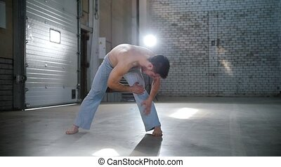 A man warming up before the capoeira training. Bending down....
