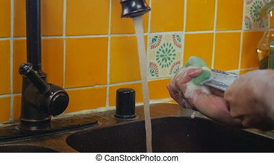 A man washes a knife with a sponge in a kitchen sink