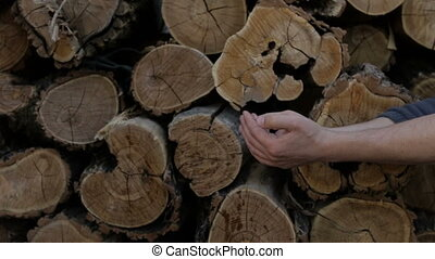 A man washes his hands on the background of cut logs