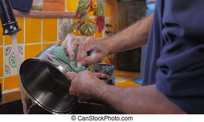 A man washing a stainless steel pot in kitchen sink