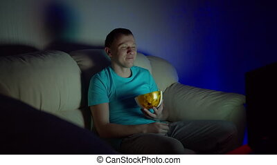 Man watching a funny movie sitting late at night at the TV with a bowl of chips, sitting on the couch