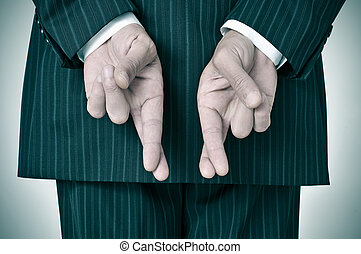 man wearing a suit crossing his fingers in his back - a man...