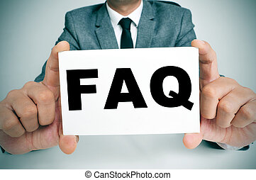 a man wearing a suit sitting in a desk holding a signboard with the word FAQ, Frequently Asked Questions, written in it