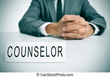 a man wearing a suit sitting in a desk with a desktop nameplate in front of him with the word counselor