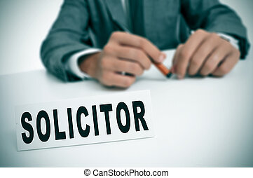 solicitor - a man wearing a suit sitting in a desk with a...