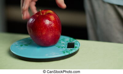 A man weighs a fresh red apple on a kitchen scale, close-up...