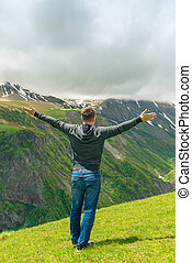 A man who admires the beautiful mountain peaks, view from the back with arms outstretched
