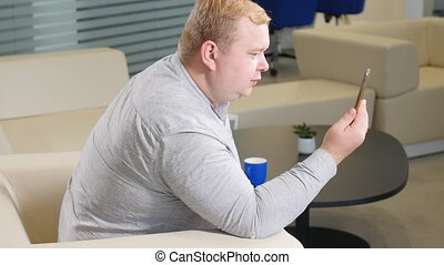 A man who is overweight talks on a video call phone