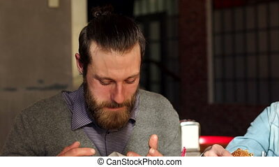 A man wipes his mouth with a napkin during lunch at a restaurant.