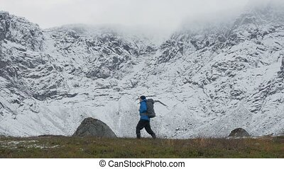 A man with a backpack, alone, traveling in the mountains. It goes along high snowy peaks.