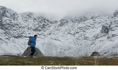 A man with a backpack, alone, traveling in the mountains. It he goes along high snowy peaks.