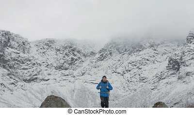 A man with a backpack goes on the background of large mountains.
