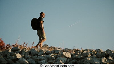 A man with a backpack looking into the distance and is on the mountain. Healthy Active Lifestyle.