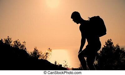 A man with a backpack rises to the top of the mountain at sunset. Silhouette of the person at sunset. Healthy Active Lifestyle.