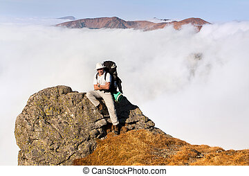 A man with a backpack sitting on the edge of a cliff in the mountains