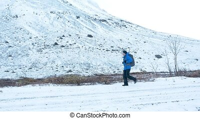 A man with a backpack travels on a snowy road. It goes along a high ridge.