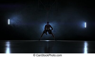 A man with a basketball on a dark basketball court against...