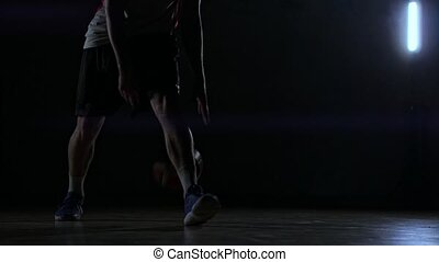 A man with a basketball on a dark basketball court against...