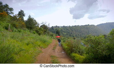 A man with a beard and a red umbrella walking on dirt road -...