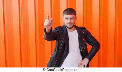 A man with a beard and in a leather jacket points his finger at the camera on an orange background, copy space, caucasian, slow-mo