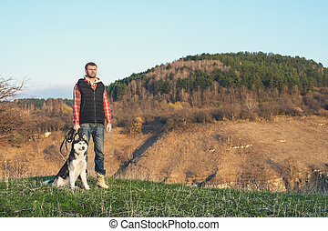 A man with a beard walking his dog in the nature, standing with a backlight at the rising sun, casting a warm glow and long shadows against the background of the gorge and trees.