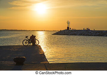 A man with a bicycle on the pier at sunset.
