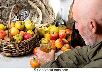 man with a bottle and glass of cider, apples at background