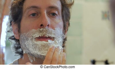 A man with a full beard applies shaving cream to his face - handheld