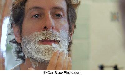 A man with a full beard applies shaving cream to his face -...